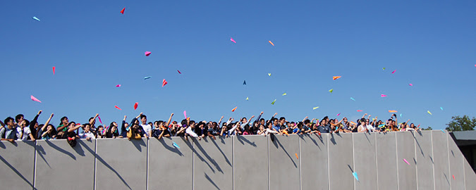 Students throwing paper airplanes